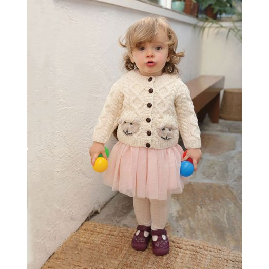 Baby modelling Aran Woollen Mills handknit wool cardigan sweater with sheep pockets