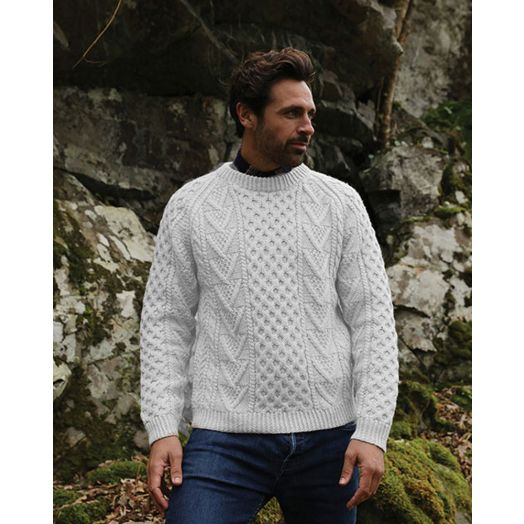 Model wearing an Aran handknit crew neck sweater in a natural colour